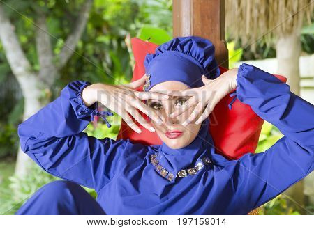 attractive woman in a Muslim swimwear burkini in gazebo for rest in a garden looks through the fingers
