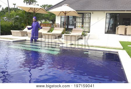 attractive woman in a Muslim swimwear burkini enters in the pool in a tropical garden