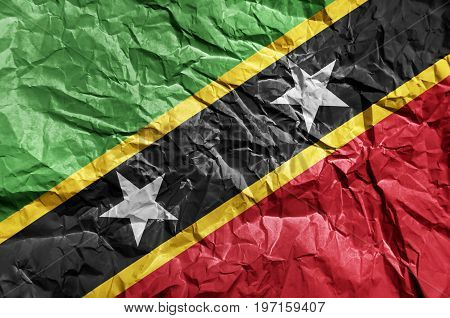 Saint Kittis and Nevis flag painted on crumpled paper background