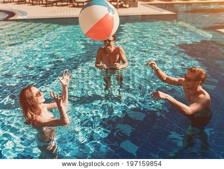 Group of young people are having fun in swimming pool playing with inflatable ball and smiling.