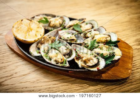Seafood. Shellfish mussels. Baked mussels with cheese, parsley and lemon in shells served on a stone board.