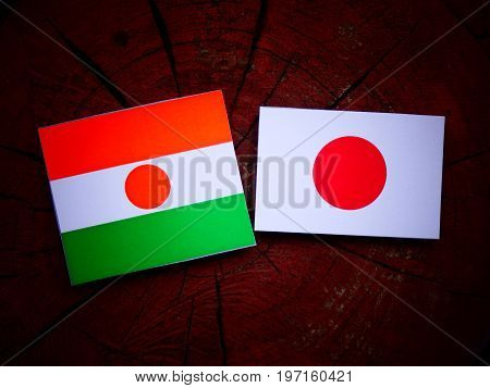 Niger Flag With Japanese Flag On A Tree Stump Isolated