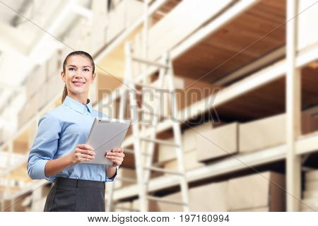Young worker with tablet at storehouse. Wholesale and logistic concept