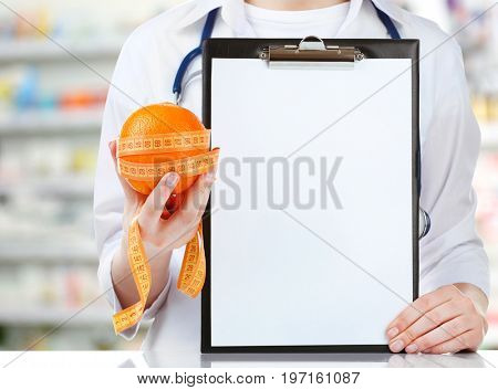 Nutritionist holding orange with measure tape and clipboard at pharmacy