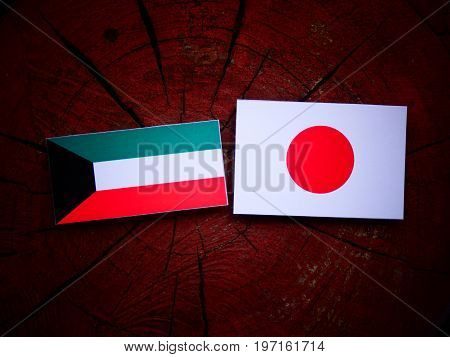 Kuwaiti Flag With Japanese Flag On A Tree Stump Isolated