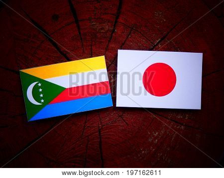 Comoros Flag With Japanese Flag On A Tree Stump Isolated