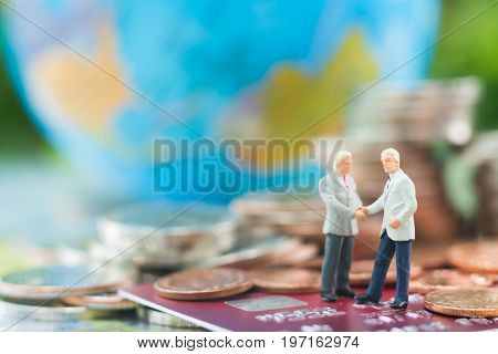 Miniature businessman handshaking and standing on the credit card or debit card with blurred globe and stacks of coins background using as commitment agreement investment partnership E-commerce and online business concept.