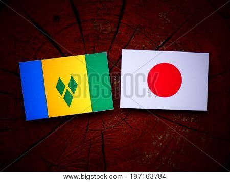 Saint Vincent And The Grenadines Flag With Japanese Flag On A Tree Stump Isolated