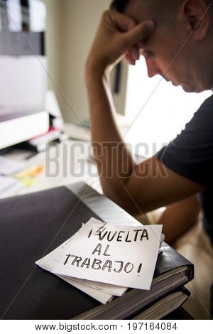 closeup of a concerned man sitting at his office desk and a note in the foreground with the text vuelta al trabajo, back to work written in spanish
