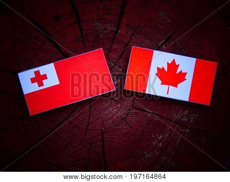 Tongan Flag With Canadian Flag On A Tree Stump Isolated