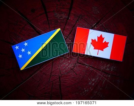 Solomon Islands Flag With Canadian Flag On A Tree Stump Isolated