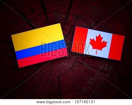 Colombian Flag With Canadian Flag On A Tree Stump Isolated
