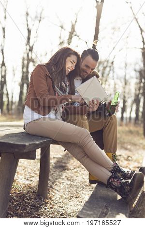Couple in love sitting on a wooden bench in the forest on a beautiful autumn day holding a tablet computer and searching for hiking tracks. Focus on the girl