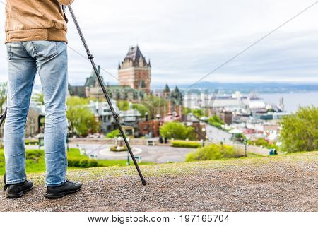 Man taking pictures on tripod of cityscape or skyline of Chateau Frontenac park and old town streets during sunset