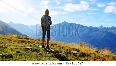 Hiker looks at the alpine landscape in the Canton Graubunden - Switzerland.