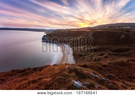 Editorial Swansea, UK - July 24, 2017: Sunset over Tor Bay and Penmaen village on the Gower peninsula in Swansea, UK's first designated Area of Outstanding Natural Beauty, South Wales, UK