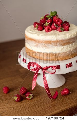 Sponge cake with whipped cream and raspberries on wooden background.