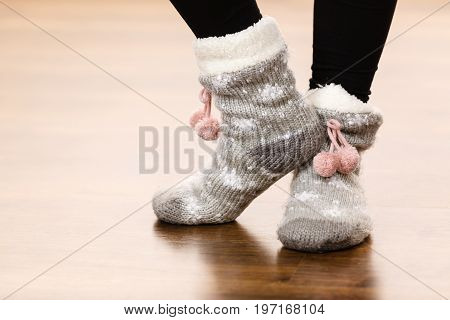 Fashion clothing winter time concept. Woman feet wearing woolen warm sock on floor.