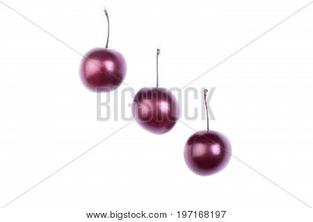 Close-up of three red cherry plums, isolated on a white background. Sweet plum. Some ripe plums. Passion fruit. Three summer berries. Whole and perfectly round plums full of vitamins. .
