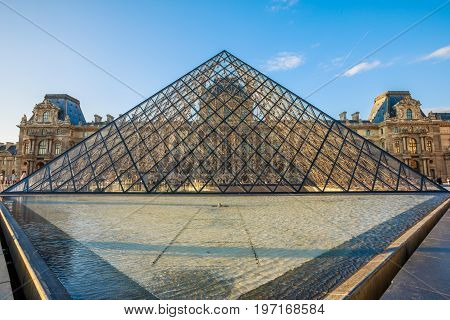 PARIS, FRANCE - JULY 1, 2017: Louvre Museum pyramid, bottom view fountain pool in the museum courtyard in Paris. French cultural picture gallery landmark hosting Gioconda painting by Leonardo da Vinci
