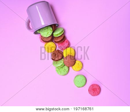 Colorful pastry made of egg whites and almond flour on a pink background French cookies macaron