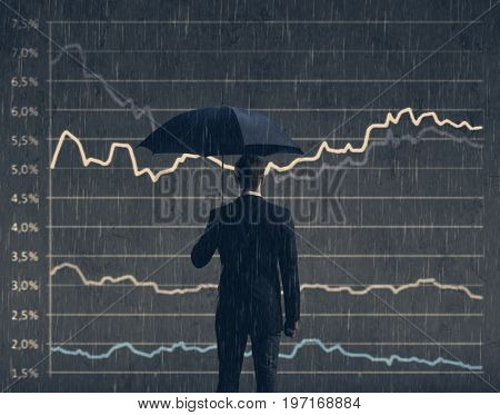 Businessman with umbrella standing over diagram background. Business, crisis, collapse, concept.