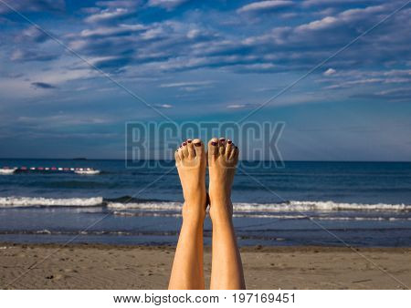 Young Girl's Tanned Legs In The Air On A Sandy Beach With Blue Sea And Sky In The Background During