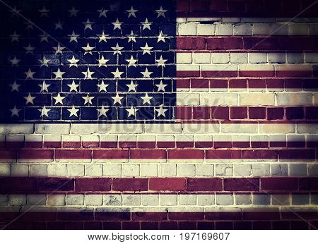 Desaturated United States of America flag on a brick wall background with a dark vignette