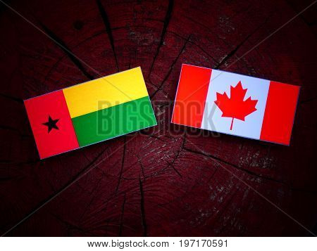 Guinea Bissau Flag With Canadian Flag On A Tree Stump Isolated