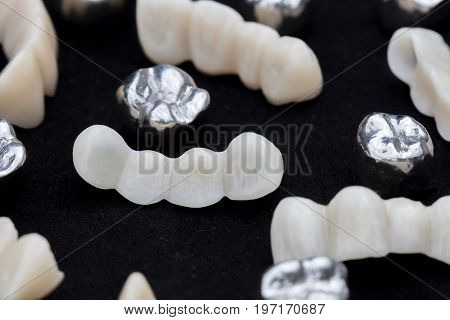 Dental silver metal tooth crowns and ceramic or zirconium tooth bridges on dark black surface.