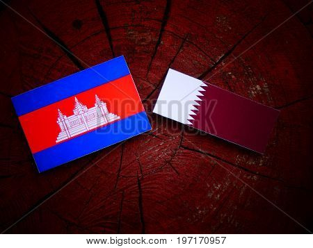 Cambodian Flag With Qatari Flag On A Tree Stump Isolated