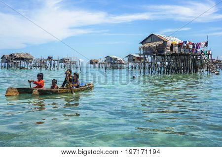 Semporna,Sabah,Malaysia-Apr 23,2017:Sea Gypsy kids on unique handmade boats surrounded by beautiful clear water of the Bodgaya island,Semporna,Sabah,Malaysia.