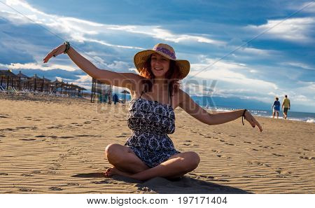 Happy Cheerful Summertime Woman Wearing Dress And Hat Sitting On The Beach With Sunshades And Blue S