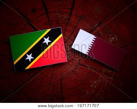 Saint Kitts And Nevis Flag With Qatari Flag On A Tree Stump Isolated