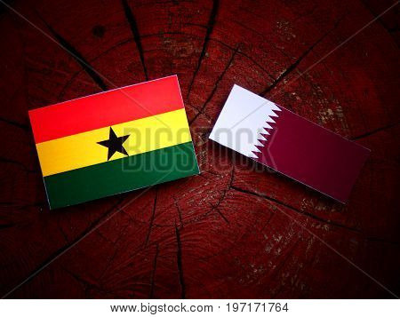 Ghanaian Flag With Qatari Flag On A Tree Stump Isolated