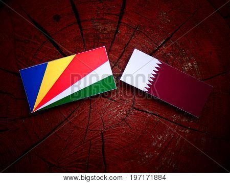 Seychelles Flag With Qatari Flag On A Tree Stump Isolated