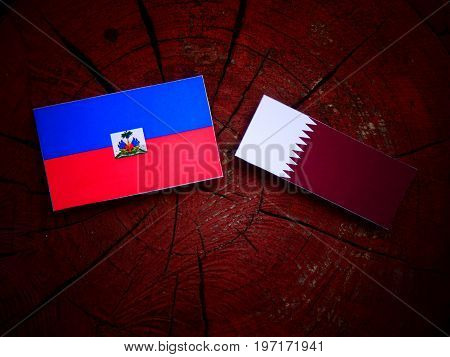 Haitian Flag With Qatari Flag On A Tree Stump Isolated