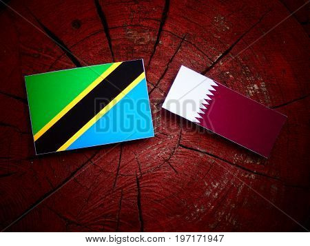 Tanzanian Flag With Qatari Flag On A Tree Stump Isolated