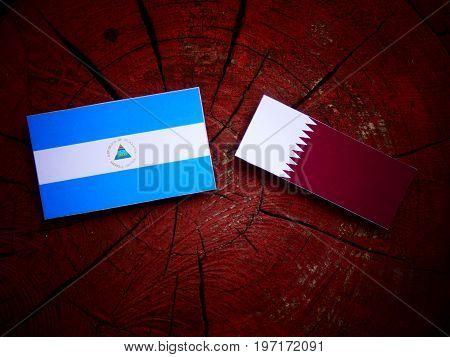 Nicaraguan Flag With Qatari Flag On A Tree Stump Isolated