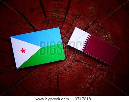 Djibouti Flag With Qatari Flag On A Tree Stump Isolated