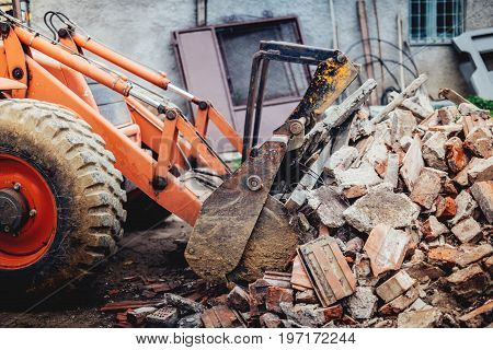 Bulldozer Demolishing An Old Building And Carrying Debris Into Dumper Trucks