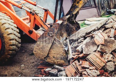 Bulldozer Demolishing Concrete Brick Walls Of Small Building And Gathering Debri, Loading Into Dumpe