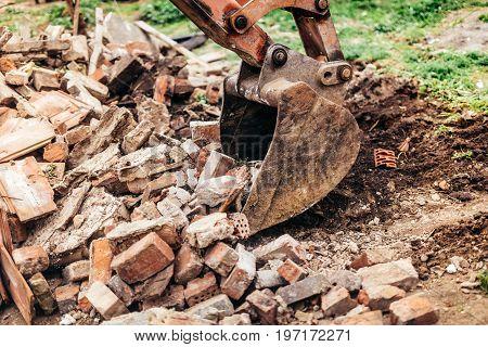 Backhoe Excavator Demolishing Building And Gathering Debris During House Construction