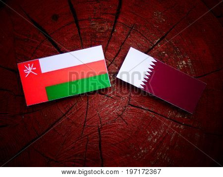 Omani Flag With Qatari Flag On A Tree Stump Isolated