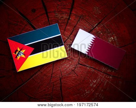 Mozambique Flag With Qatari Flag On A Tree Stump Isolated