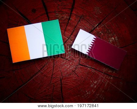 Ivory Coast Flag With Qatari Flag On A Tree Stump Isolated