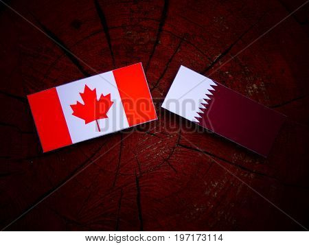 Canadian Flag With Qatari Flag On A Tree Stump Isolated