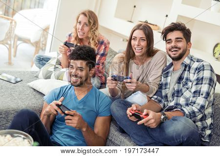 Group of friends relaxing and playing video game and smiling at home together.
