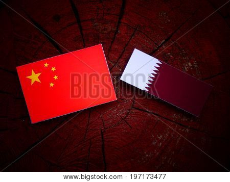 Chinese Flag With Qatari Flag On A Tree Stump Isolated