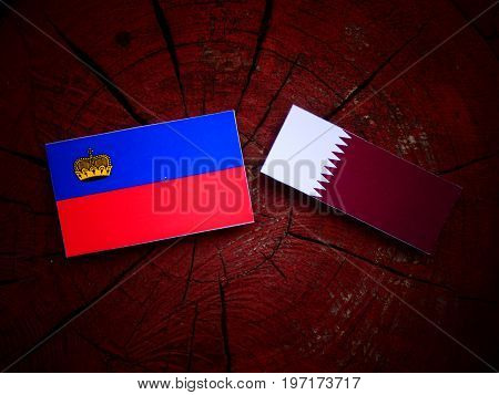 Liechtenstein Flag With Qatari Flag On A Tree Stump Isolated